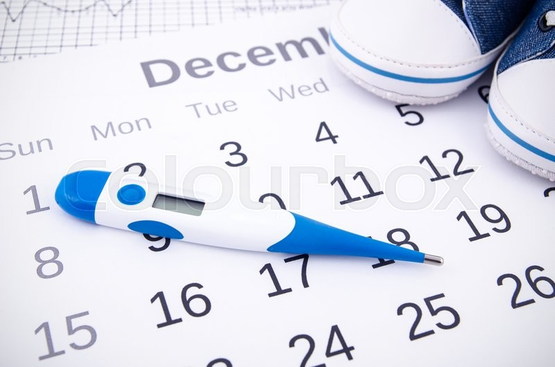 Stock image of 'Electronic thermometer in fertility concept on calendar'
