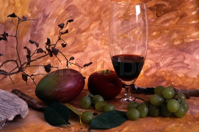 Stock image of 'A glass red wine and fruits isolated on painted background'