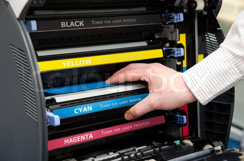Stock image of 'Man puts toner in the printer'
