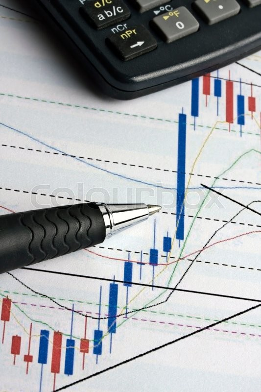 Stock image of 'Analyzing the stock market with calculator amd pen'