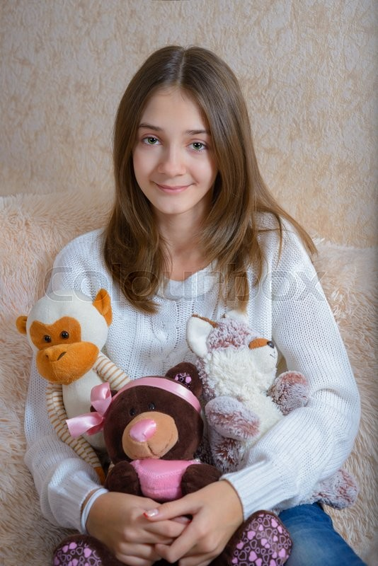 Stock image of 'Girl with toys sitting on the couch with a fur coverlet'
