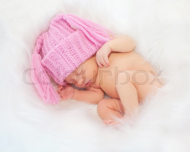 Stock image of 'Sleeping newborn baby in the white fur. Birth and a new life concept.'