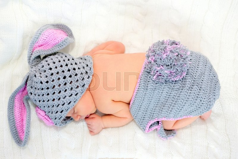 Stock image of 'Sleeping newborn baby dresses as Easter bunny on a knitted blanket'