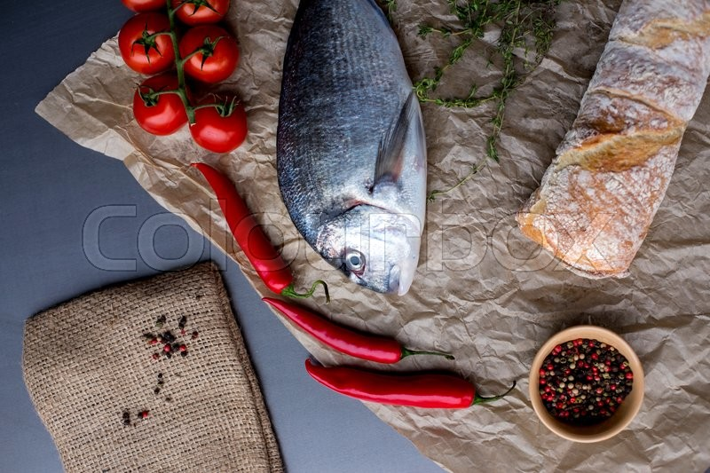 Stock image of 'Dorado fish on slate board with cherry tomatoes, lemon, garlic, rosemary, chilly pepper and peppercorns. Top view'