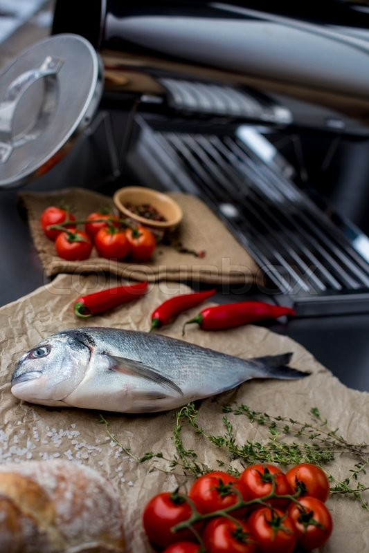 Stock image of 'High angle view of grilled and garnished whole fish on table surrounded by other dishes'