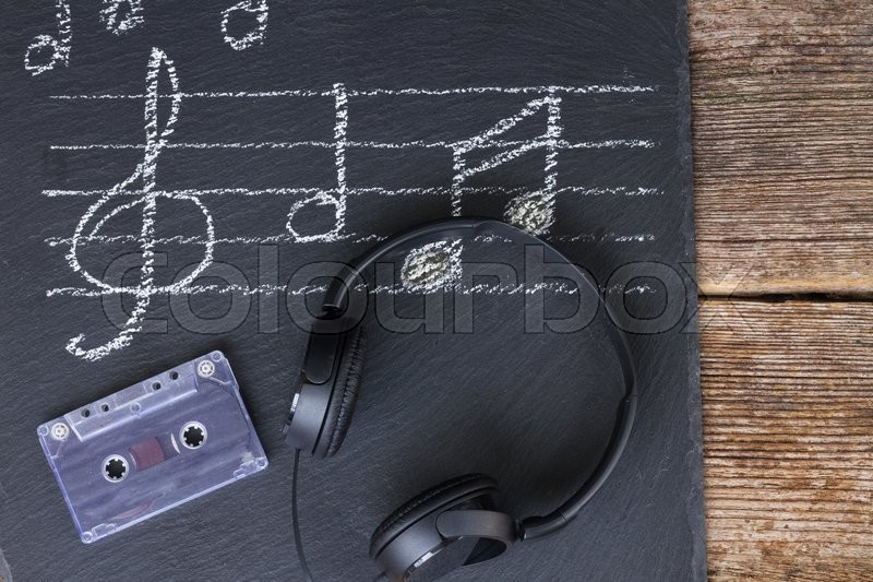Stock image of 'Music notes and treble clef with old audio cassette and headphones '