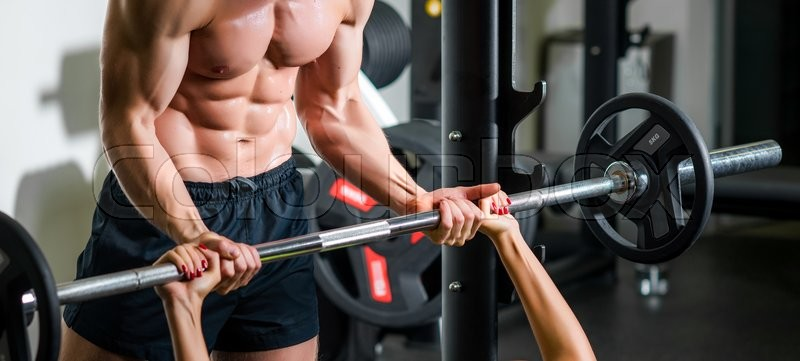 Stock image of 'weightlifting and people concept - personal trainer with barbell flexing muscles in gym'