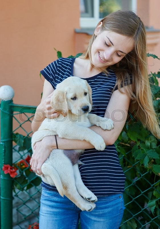 Stock image of 'beautiful blond woman playing with a puppy Labrador.'
