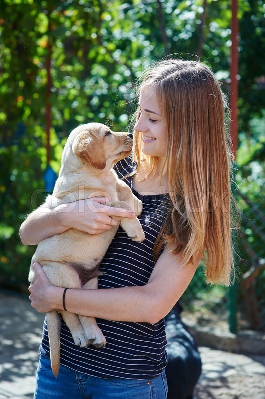 Stock image of 'blond woman playing with a white Labrador puppy.'