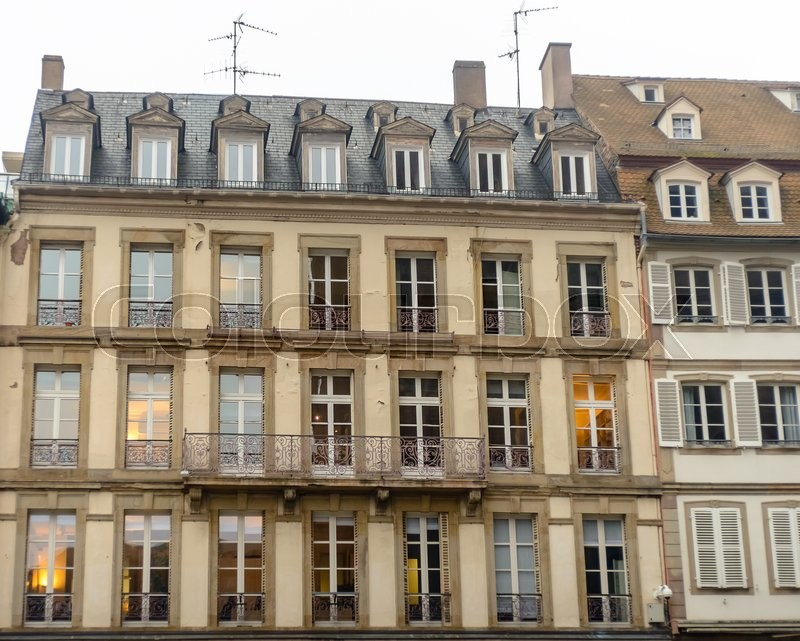 Stock image of 'The facade of french building in modern style with windows and french balconies'