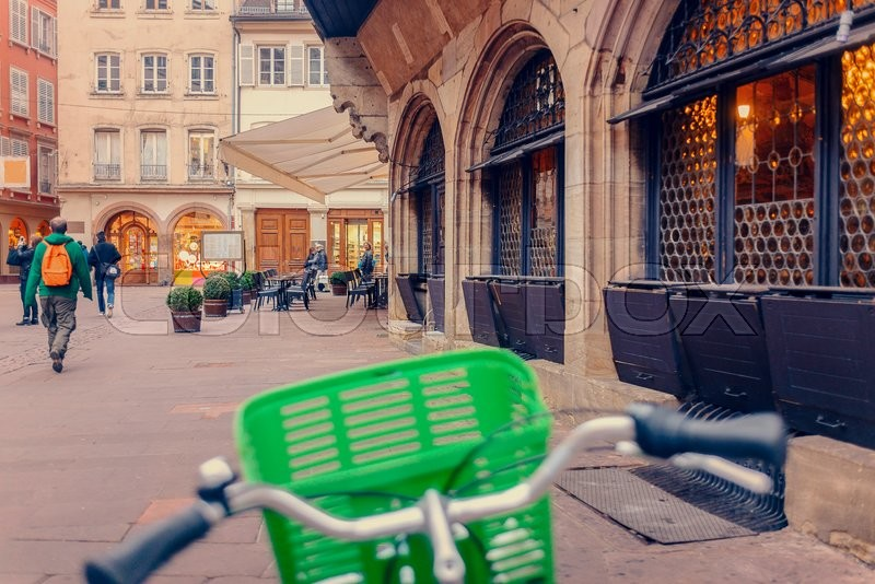 Editorial image of 'Bicycle with a colorful green basket on the handlebars parked outside a commercial urban building in a concept of eco-friendly transport'