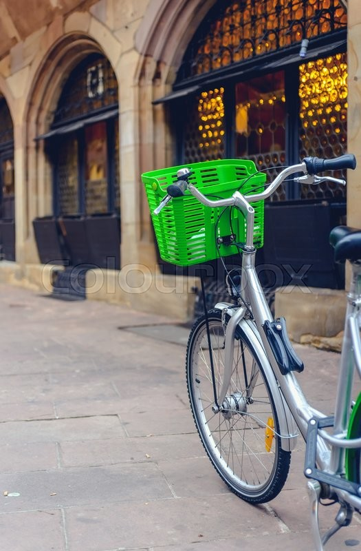 Stock image of 'Bicycle with a colorful green basket on the handlebars parked outside a commercial urban building in a concept of eco-friendly transport'