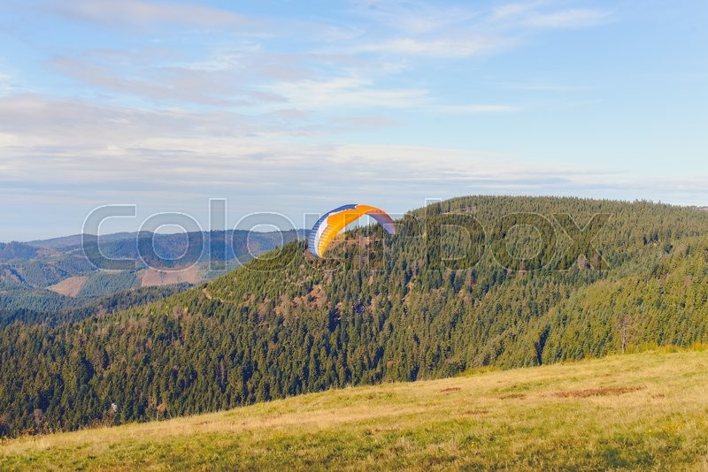 Stock image of 'Paraglider flying over mountains in summer day'
