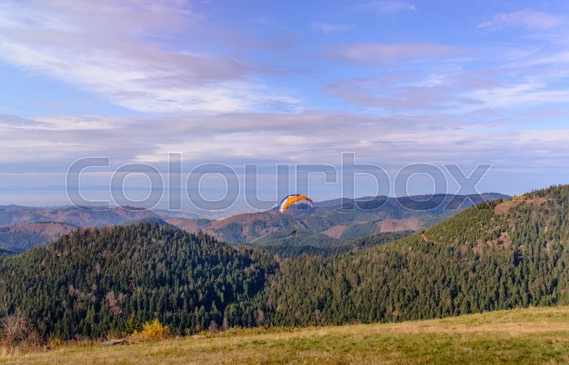 Stock image of 'PARAGLIDER OVER FARMED LAND IN BEAUTIFUL SUNSET LIGHT, SEEN FROM AIR'