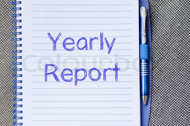 Stock image of 'Yearly report text concept write on notebook with pen'