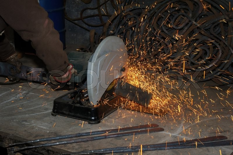 Stock image of 'Heavy industry worker cutting steel with angle grinder'
