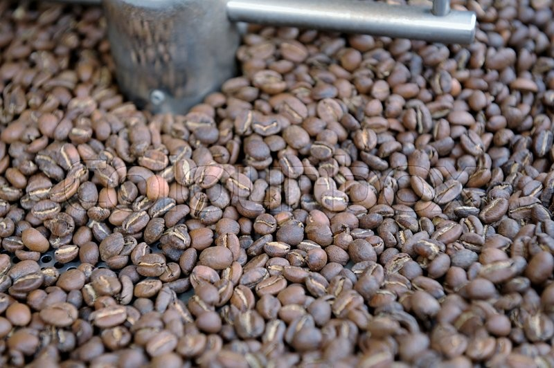 Stock image of 'Freshly roasted coffee beans in a coffee roaster'