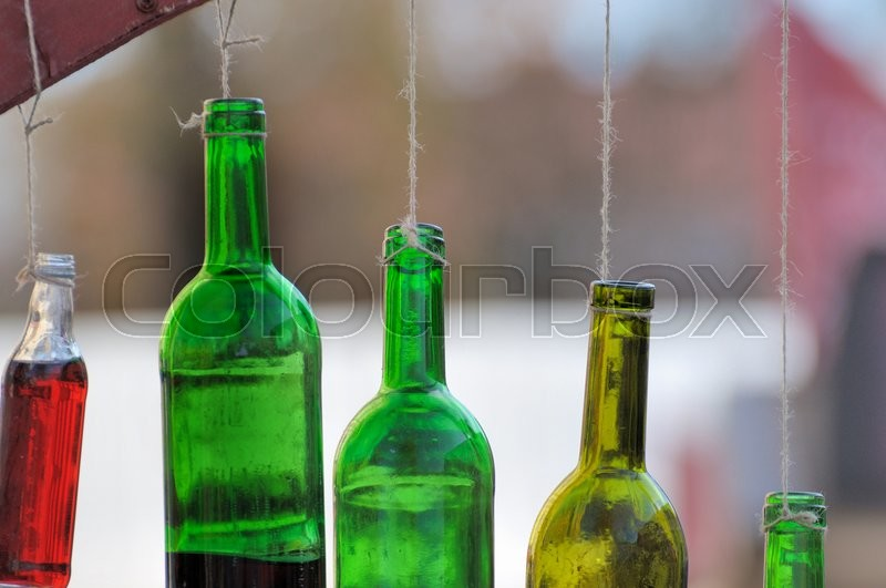 Stock image of 'Bottle of wine hanging on a cord'