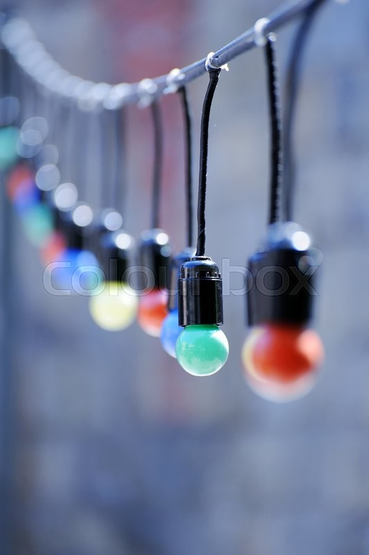 Stock image of 'Colored incandescent bulbs hanging on street'