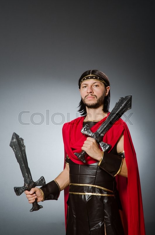 Stock image of 'Roman warrior with sword against background'