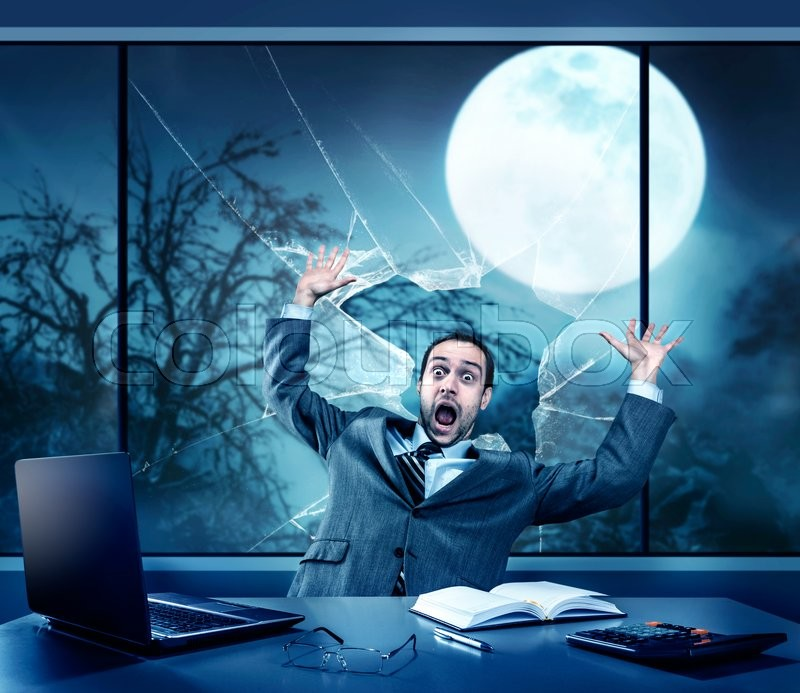 Scared businessman in the office, full moon outside, stock photo