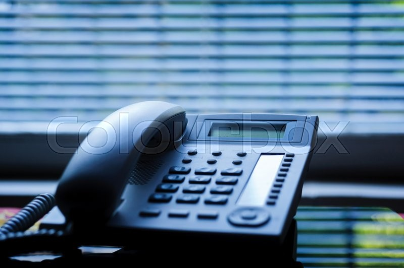 Executive VoIP desk phone with traditional corded headset and the business office window blinds in the background. Shallow depth of field - focus on the center of the phone, stock photo