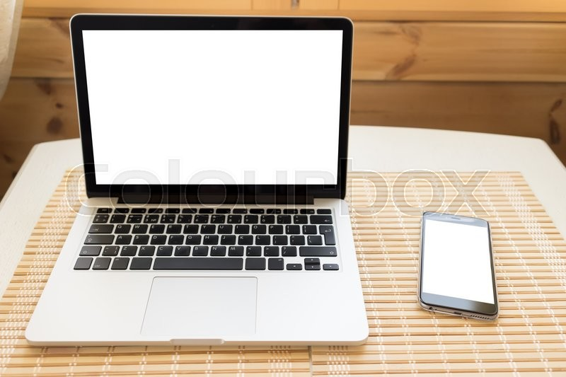 The laptop on the table with the mouse and smartphone, stock photo