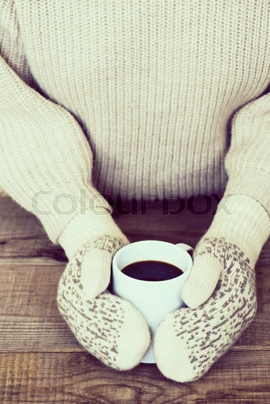 Woman hands in teal gloves are holding a mug with hot coffee or cocoa. Winter and Christmas concept, stock photo