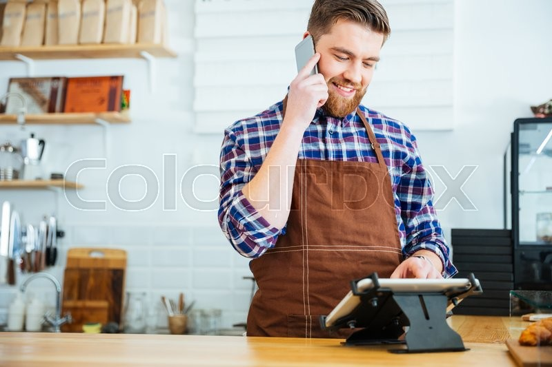 Barista taking order on cellphone and using tablet in cafeteria, stock photo