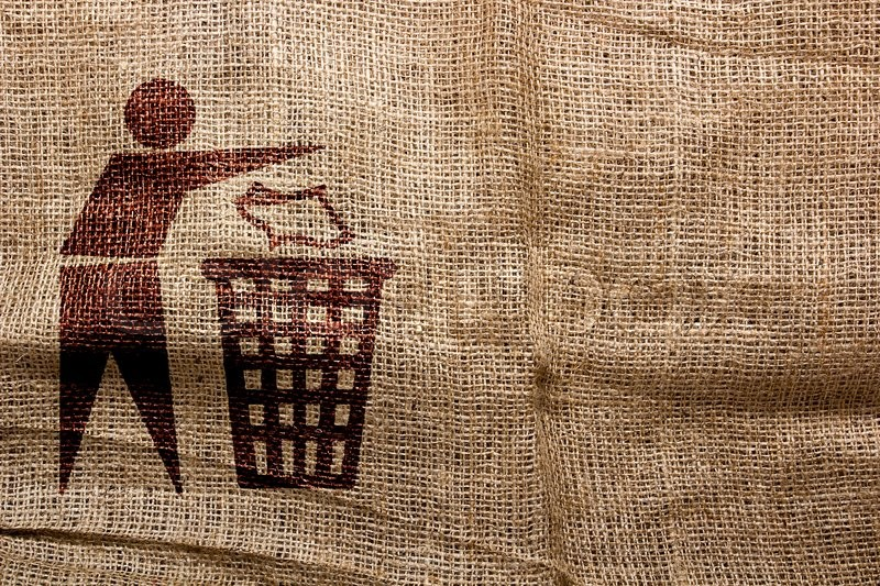 Stamp on sackcloth, throw away the trash. Industrial symbolism, stock photo