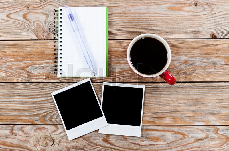 Workspace with coffee cup, instant photos, note paper and notebook on old wooden table. Business concept, stock photo