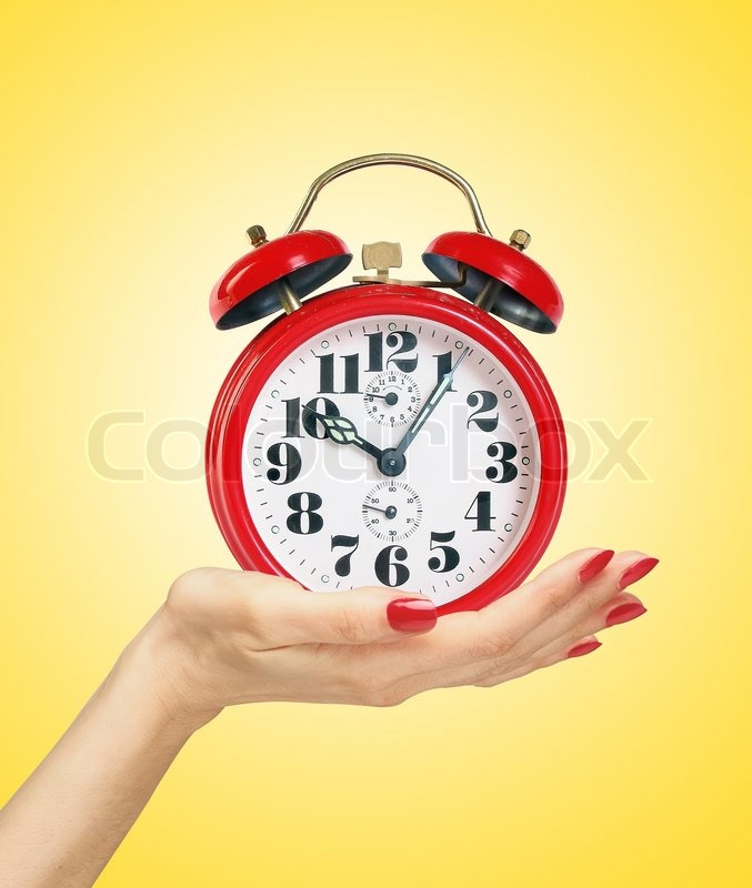 Red alarm clock in woman hand over yellow background, stock photo