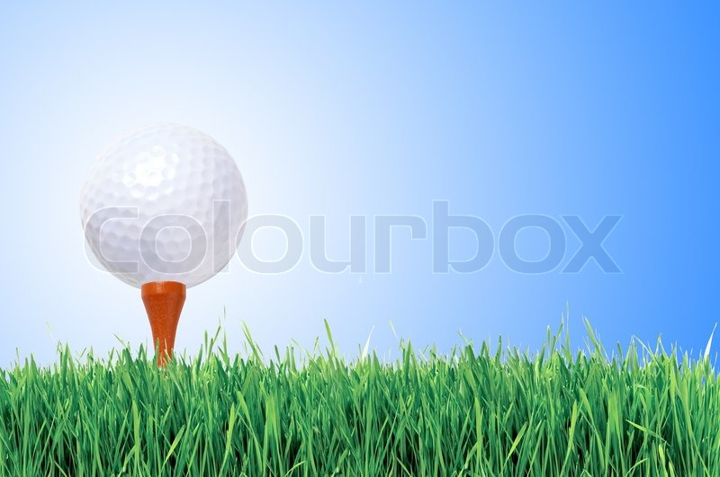 Golf ball with tee in the grass over blue sky, stock photo