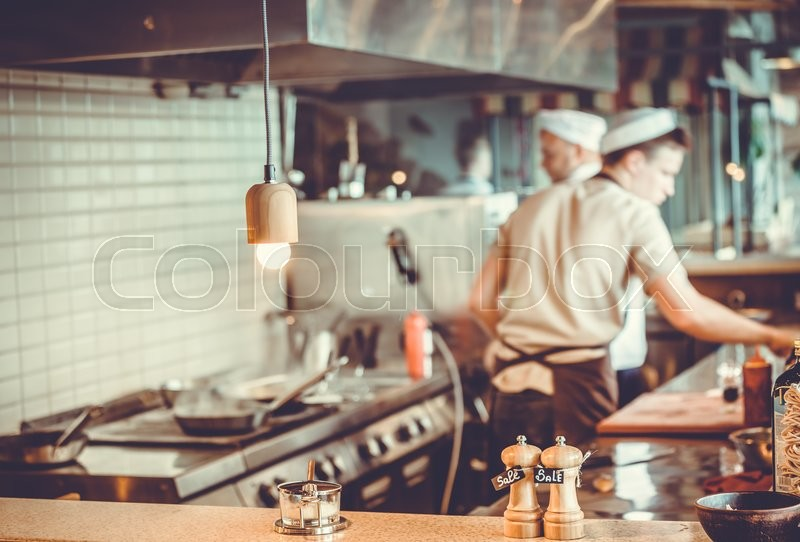 Blurred restaurant interior with salt and pepper on table, stock photo
