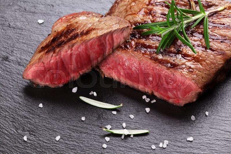 Grilled beef steak with rosemary, salt and pepper on black stone plate, stock photo