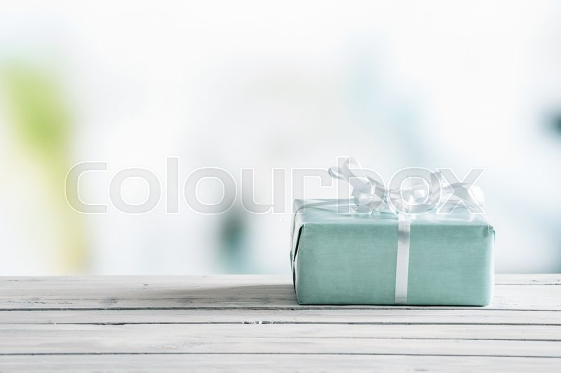 Blue gift box on a wooden table in bright light, stock photo