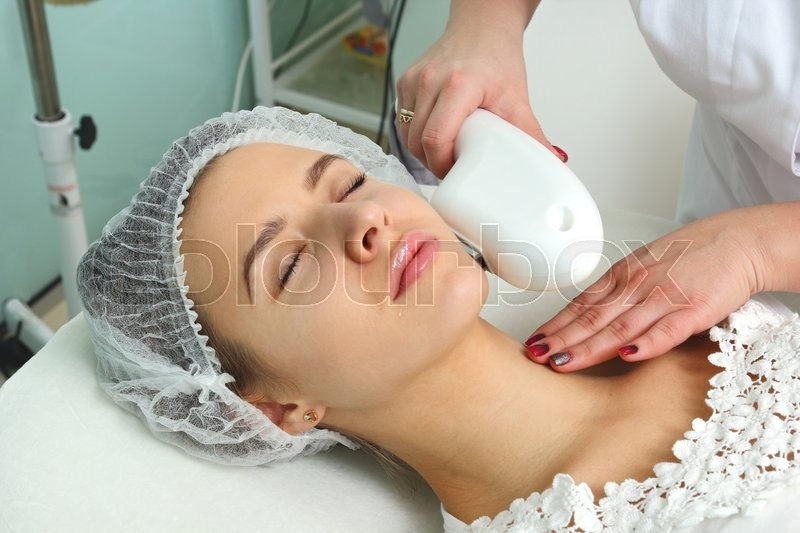 Laser hair removal in the beauty salon. Woman having facial hair removal. Laser hair removal equipment in the background, stock photo