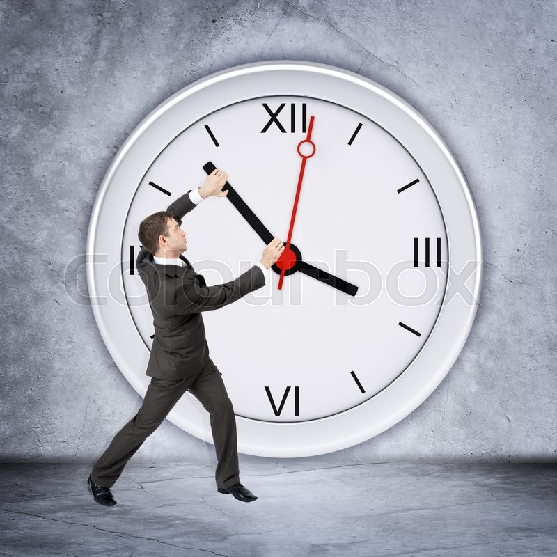 Businessman holding clock hand on grey wall backgound, side view, stock photo