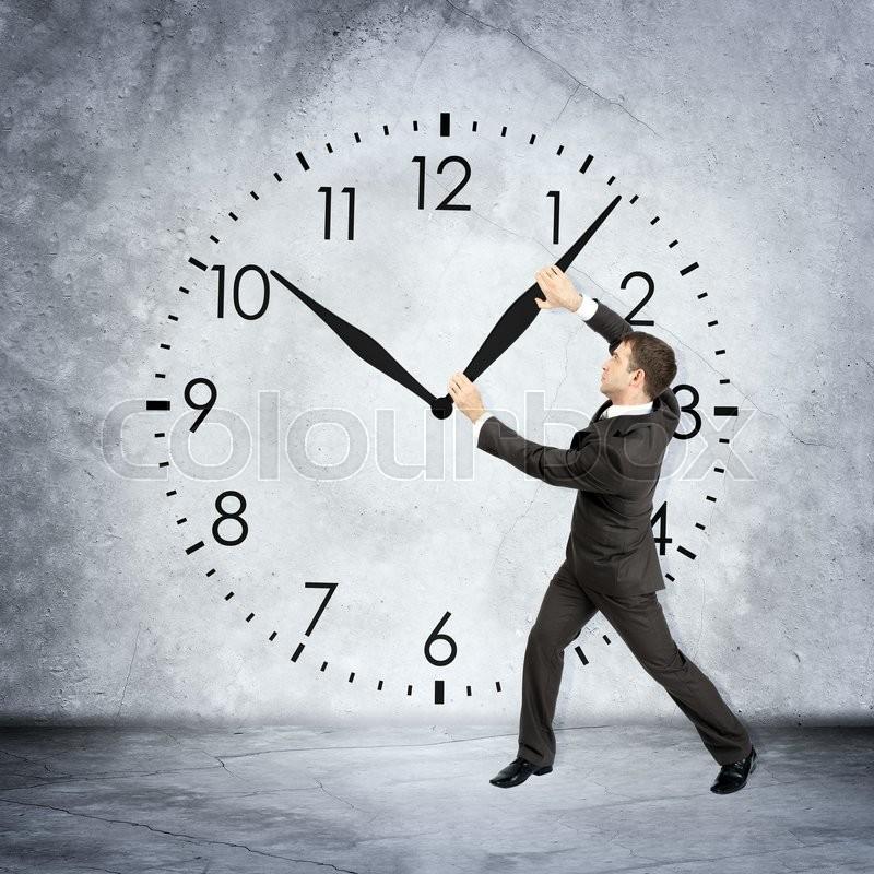 Businessman holding clock hand on grey wall backgound, stock photo