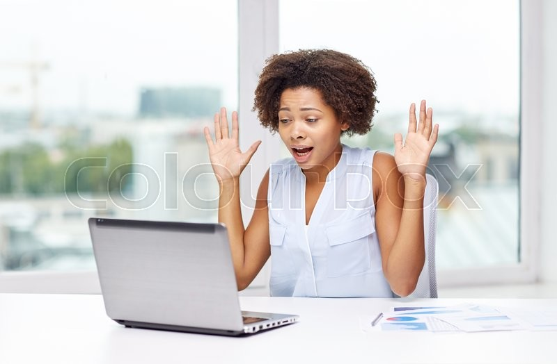 Education, business, fail and technology concept - african american businesswoman or student with laptop computer and papers at office, stock photo