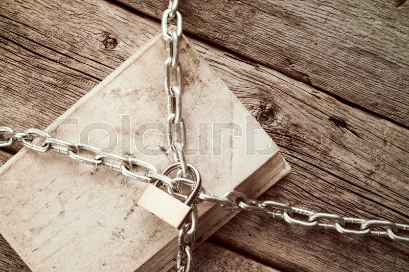 Old book with chain and padlock on wooden background.Vintage style, stock photo