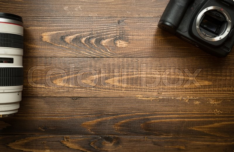 Top view of digital camera and telephoto lens on wooden background, stock photo