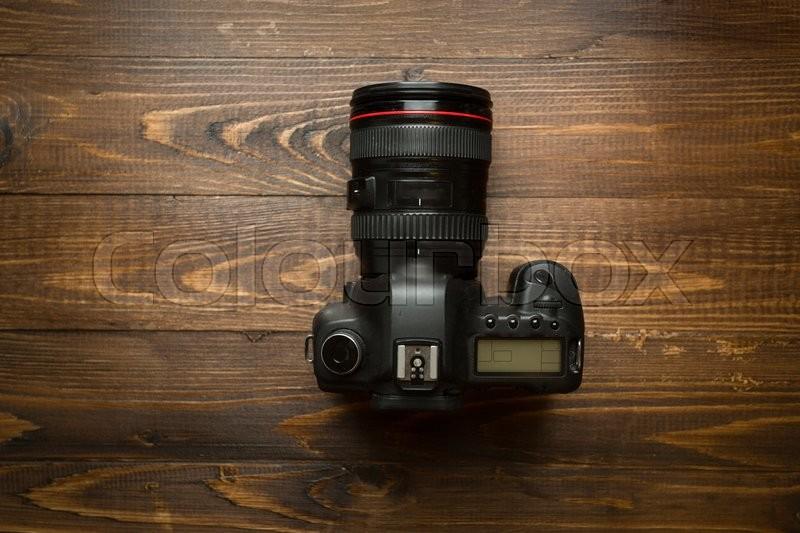 Professional digital camera on dark wooden background, stock photo