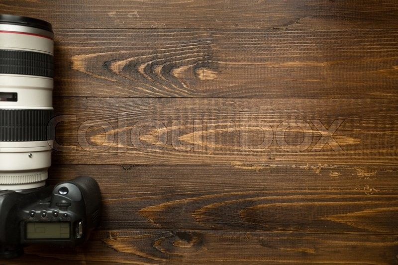 Top view of professional digital camera with telephoto lens on wooden background with copyspace, stock photo
