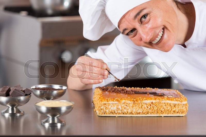 Pastry chef decorating cake yolk and cream, stock photo