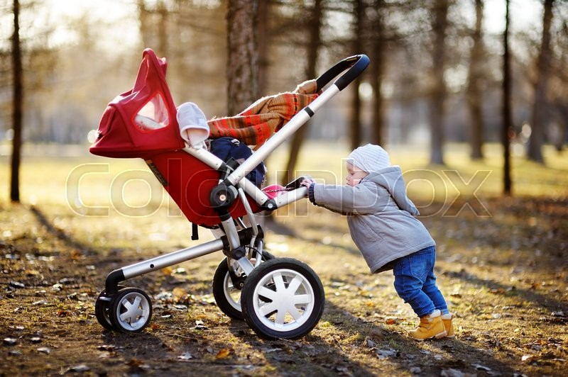 Beautiful toddler boy playing with his stroller during walking outdoors at the warm spring day, stock photo