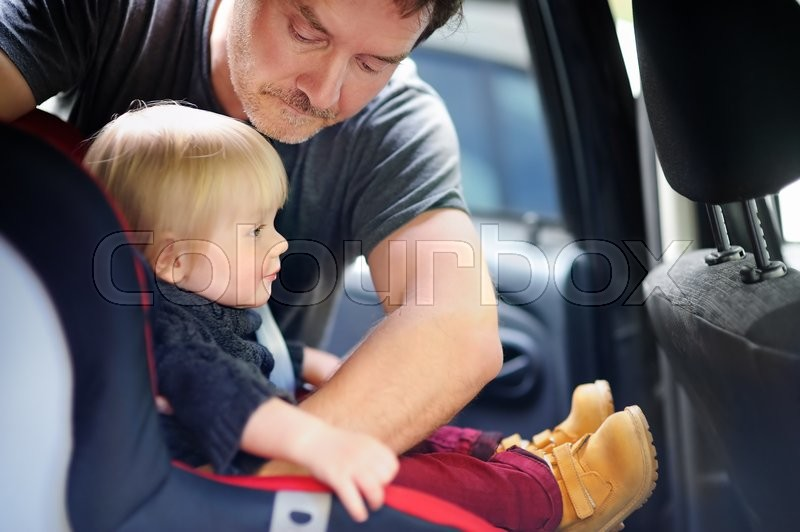 Middle age father helps his toddler son to fasten belt on car seat, focus on father, stock photo