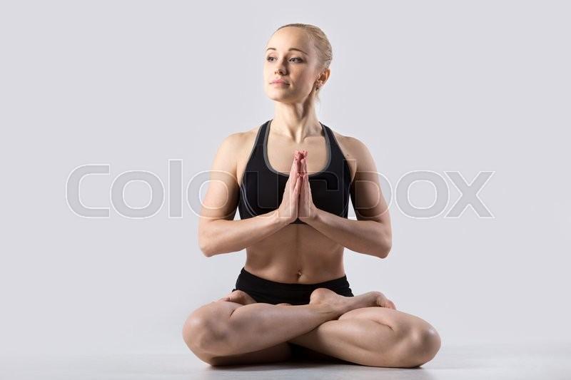 Sporty beautiful young woman practicing yoga, sitting in Padmasana, Lotus posture, asana for meditation, pranayama working out wearing black sportswear, studio, full length, stock photo