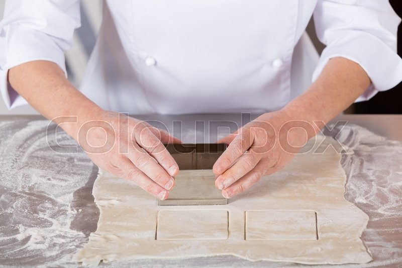 Pastry kneading a dough of a cake | Stock Photo | Colourbox