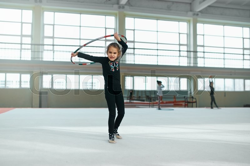 Beautiful girl gets angry with a hoop of rhythmic gymnastics, stock photo